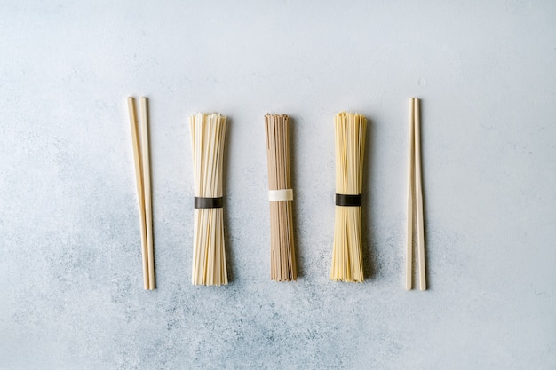 Различные виды сухой длинной азиатской лапши и палочек для еды