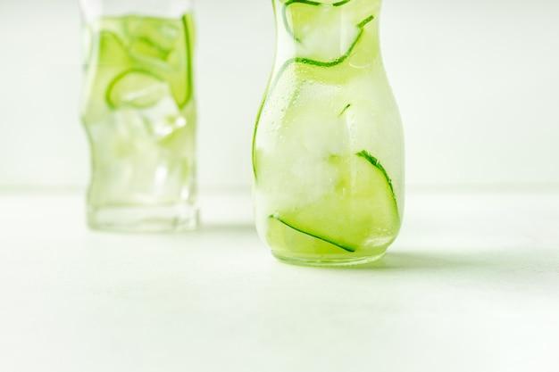 ガラスの瓶とハイボールガラス、コピースペースのクローズアップビューでキュウリ水