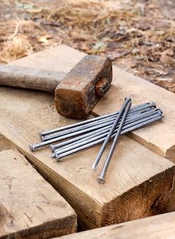 Старый ржавый молоток и гвозди, лежащие на деревянных решетках
