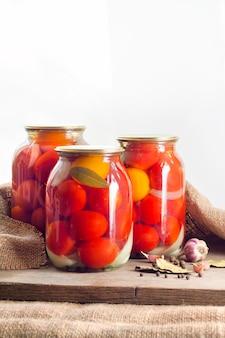 Стеклянные банки с красными маринованными помидорами, запечатанные металлической крышкой