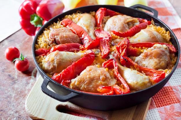 Куриные бедра и ноги, запеченные над слоем риса и красного перца