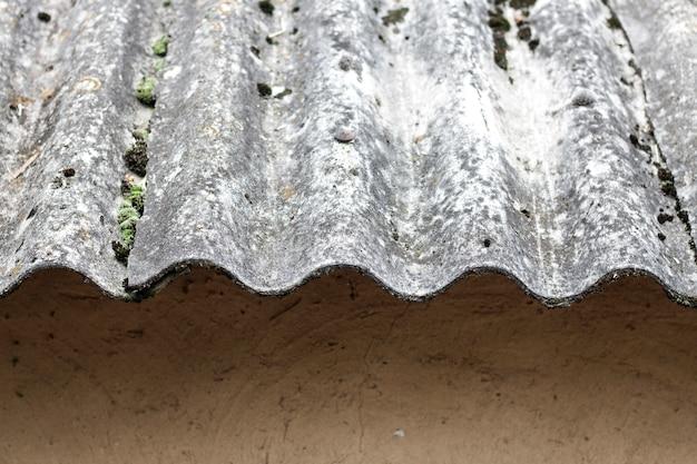 粘土の壁の上の古いスレート屋根のクローズアップ