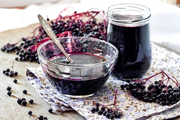 ガラスのボウルと瓶に自家製黒エルダーベリーシロップ