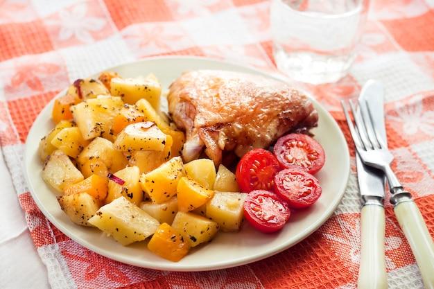 ベイクドポテトとパンプキンガーニッシュを添えたチキンモモ焼き