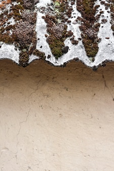 粘土の壁の上の古いスレートコケに覆われた屋根のクローズアップ