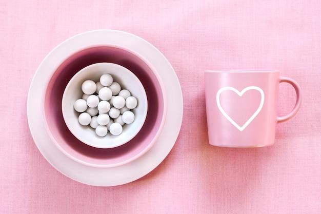 優しいピンクの布の表面にピンクのマグカップと白砂糖の糖衣錠付きプレート。平面図、平置き