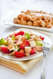 Салат из трех видов помидоров, отварной белой фасоли и сухариков из белого хлеба
