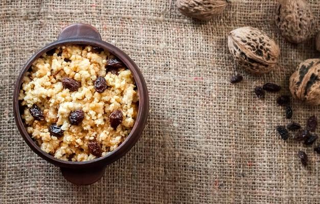 Сладкая пшенная каша с темным изюмом в керамической миске с грецкими орехами
