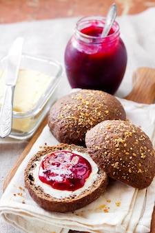 リンシード、ゴマ、ケシの実の自家製ライ麦パンにバターとジョスタベリージャムを添えて