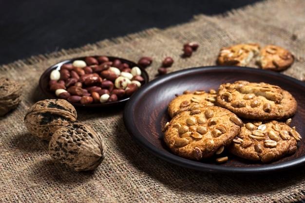 Домашнее арахисовое печенье на коричневой тарелке с сырым арахисом в поверхности