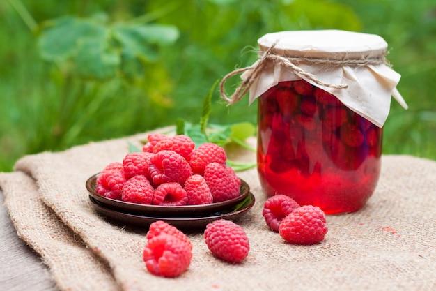 ガラスの瓶にラズベリーのジャムと皿の上の新鮮なラズベリー