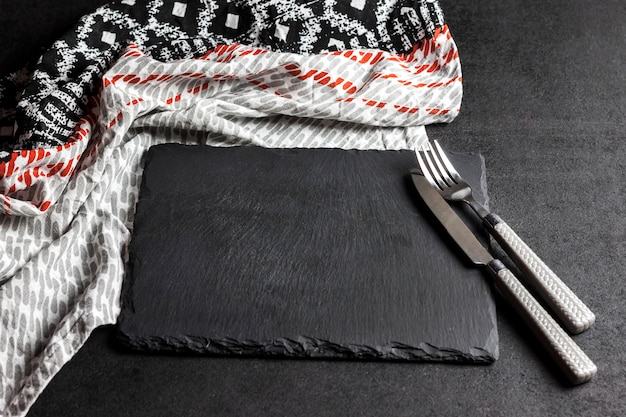 Черная грифельная тарелка с вилкой и ножом на черной поверхности и скатерть. сервировка стола.
