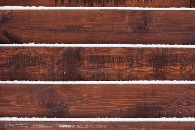 Деревянный забор фон со снегом лежал на досках