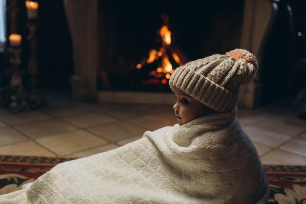 暖炉のそばに座って、笑みを浮かべて、冬時間で楽しんでいるかわいい女の子。クリスマス、新年、冬のコンセプト