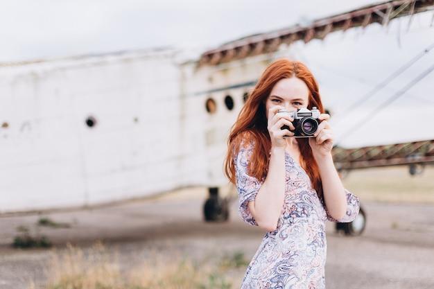 屋外で撮影するジンジャーガールカメラマン