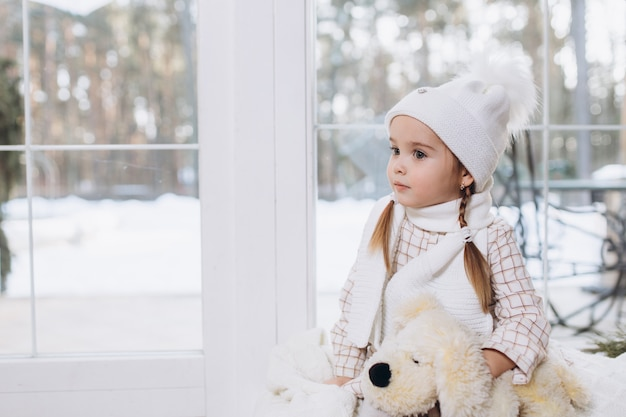 屋内でニット帽子の愛らしいかわいい女の子。クリスマス、冬休み、子供時代のコンセプト