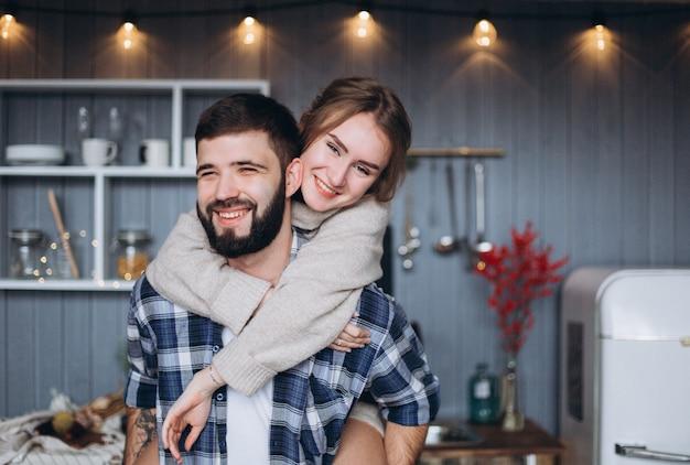 一緒に居心地の良いキッチンで幸せな若い家族
