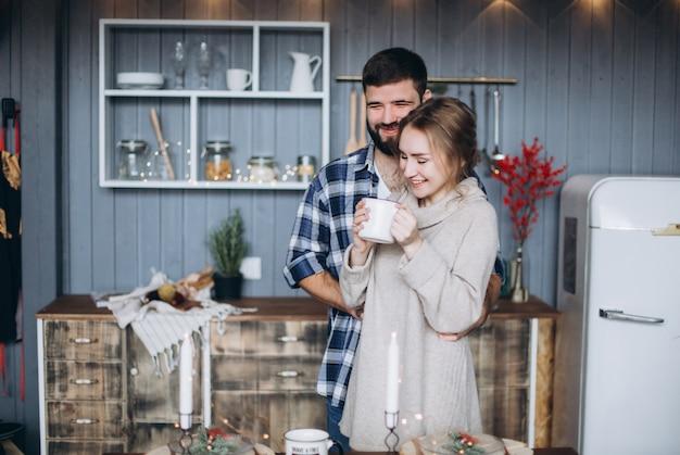 居心地の良いクリスマス装飾のキッチンで一緒に抱いて若い幸せな笑みを浮かべて陽気なカップル。
