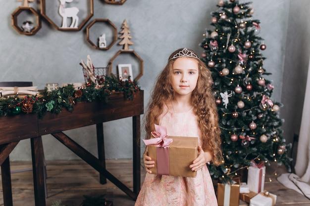 カラフルな新年のライトと居心地の良い家でお茶とクリスマスの装飾で陽気な女の子