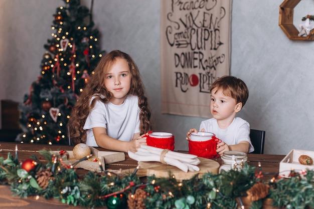 カラフルな新年のライトと居心地の良い家でお茶とクリスマスの装飾の小さな子供たち