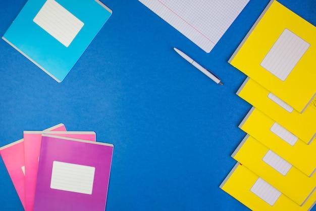 Различные красочные школьные тетради на синем