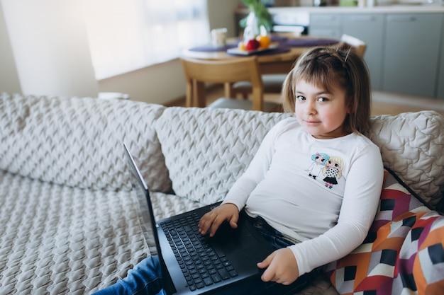 Маленькая девочка с ноутбуком на диване