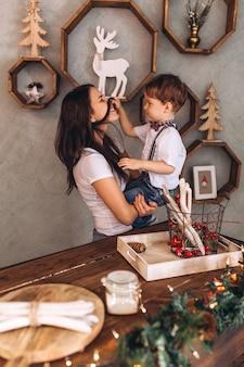 幸せな母と息子の新年のプレゼントとクリスマスイブのお祝いの装飾とクリスマスライトのクリスマスの陽気な肖像画