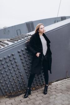 橋の近くの若いブロンディビジネス女性。ヨーロッパの街を歩く