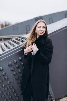 橋の近くの若い幸せなブロンディビジネス女性。ヨーロッパの街を歩く