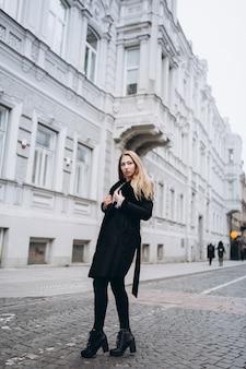 Модная красивая молодая блондинка женщина позирует в модные модные пальто на открытом воздухе. красота, мода, модельная концепция