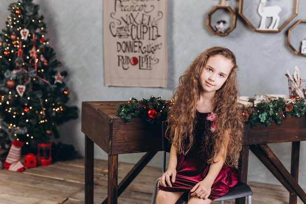 Модная красивая девушка в платье дома возле новогодней ночи и рождественские украшения и разноцветные огни