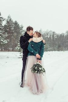 女と男の肖像画は一緒に屋外を抱き締めます。冬のアウトドア。華やかな森を一緒に歩いて愛のかわいい優しいカップルを愛する