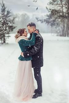 冬の季節の白人カップルの結婚式は、屋外の肖像画を閉じます。華やかな森を一緒に歩いて愛のかわいい優しいカップルを愛する