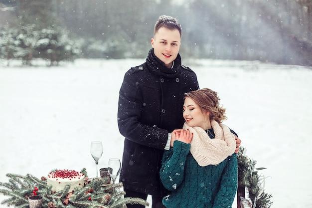 冬の白人カップルは屋外の肖像画を閉じます。華やかな森を一緒に歩いて愛のかわいい優しいカップルを愛する