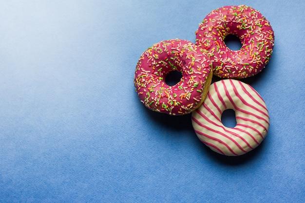 青色の背景にピンクの艶をかけられたドーナツ