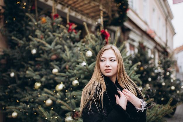 На открытом воздухе крупным планом женский портрет в рождественские украшения