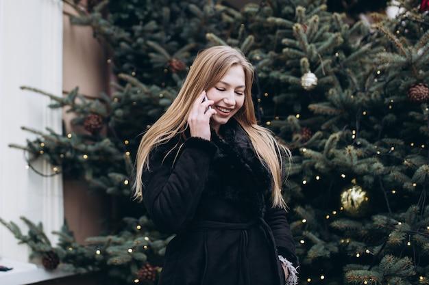 На открытом воздухе крупным планом женский портрет с смартфон в рождественские украшения