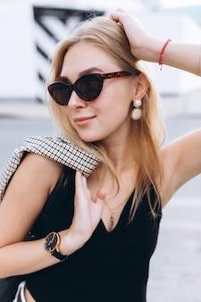 夏の日に街を歩いて黒と白の服に身を包んだ若いかわいいブロンディ少女のライフスタイル都市ファッション流行の肖像画