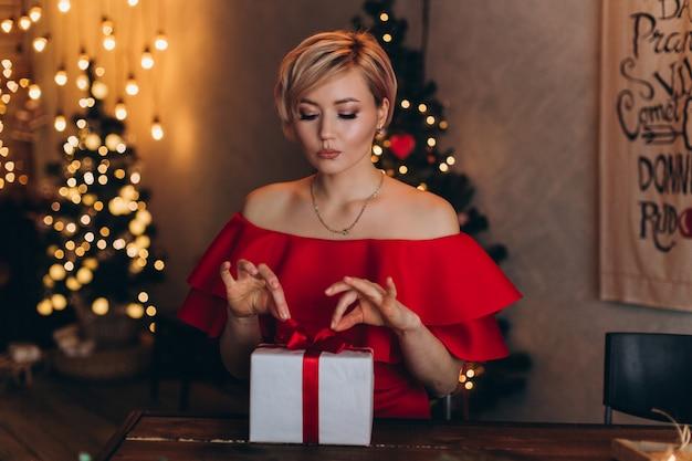 クリスマスに手で新年プレゼントボックスと赤いドレスの若い幸せな陽気な女性の肖像画は、家に飾られています。クリスマス、幸福、美容、プレゼントのコンセプト