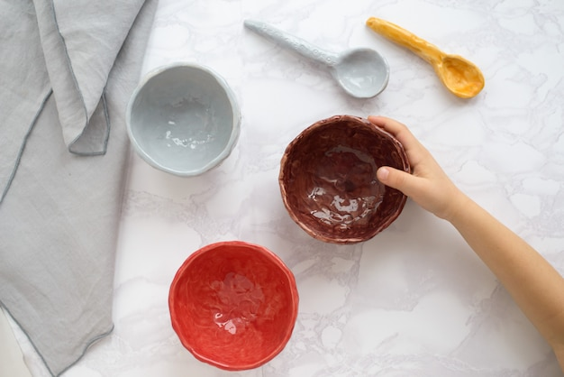 Гончарная мастерская, разноцветные керамические тарелки, вид сверху