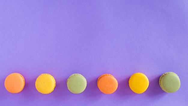 薄紫色の背景、フラットレイアウトまたはトップビューでパステルカラーのマカロン