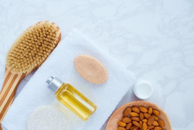 スパナチュラル化粧品アーモンドエキスと白い背景の上のタオルでフラットレイアウト構成