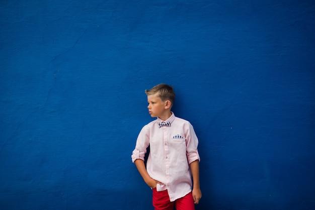 青色の背景にポーズのファッション少年