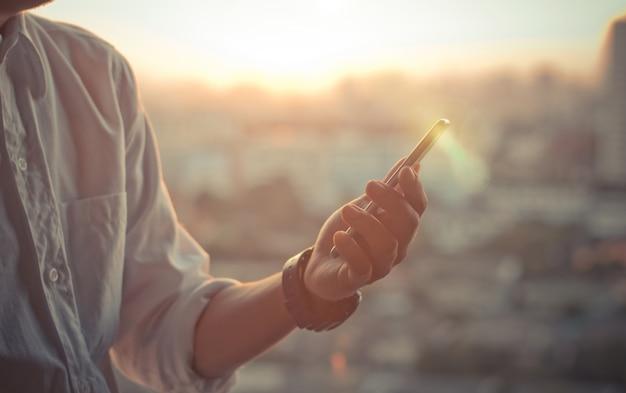 スマートフォンを使用してビジネスマンは、背景としてぼやけた都市の都市の日没の空に手