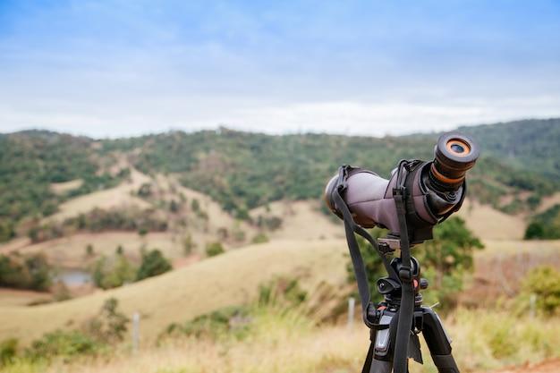ぼやけている緑の山の上のスコープまたは単眼を発見