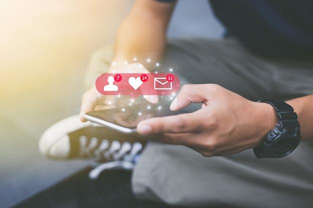 Концепция сети социальных средств массовой информации. крупным планом руки человека, с помощью мобильного телефона