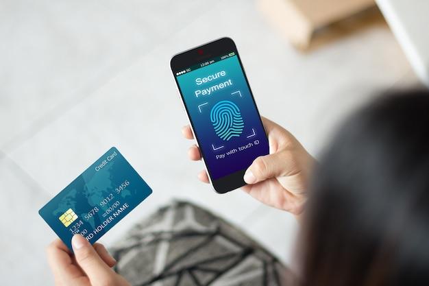 女性の手は、携帯電話とクレジットカードを使用して