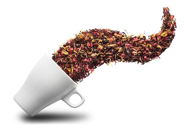 Сухой травяной чай наливание в чашку, изолированные на белой поверхности