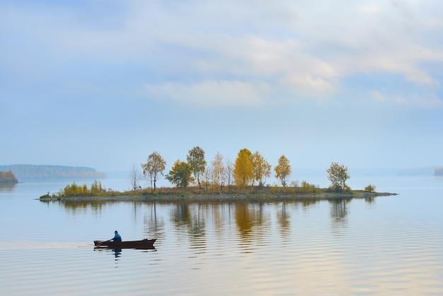 漁師は湖の島の周りを泳ぐ