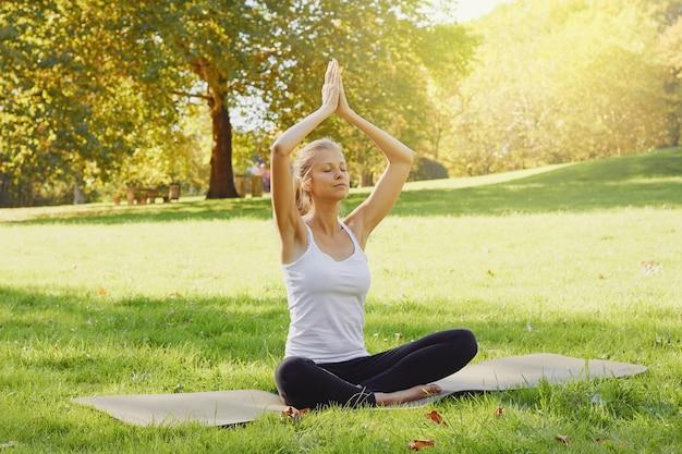 公園で屋外ヨガを練習しながら女の子が瞑想します。